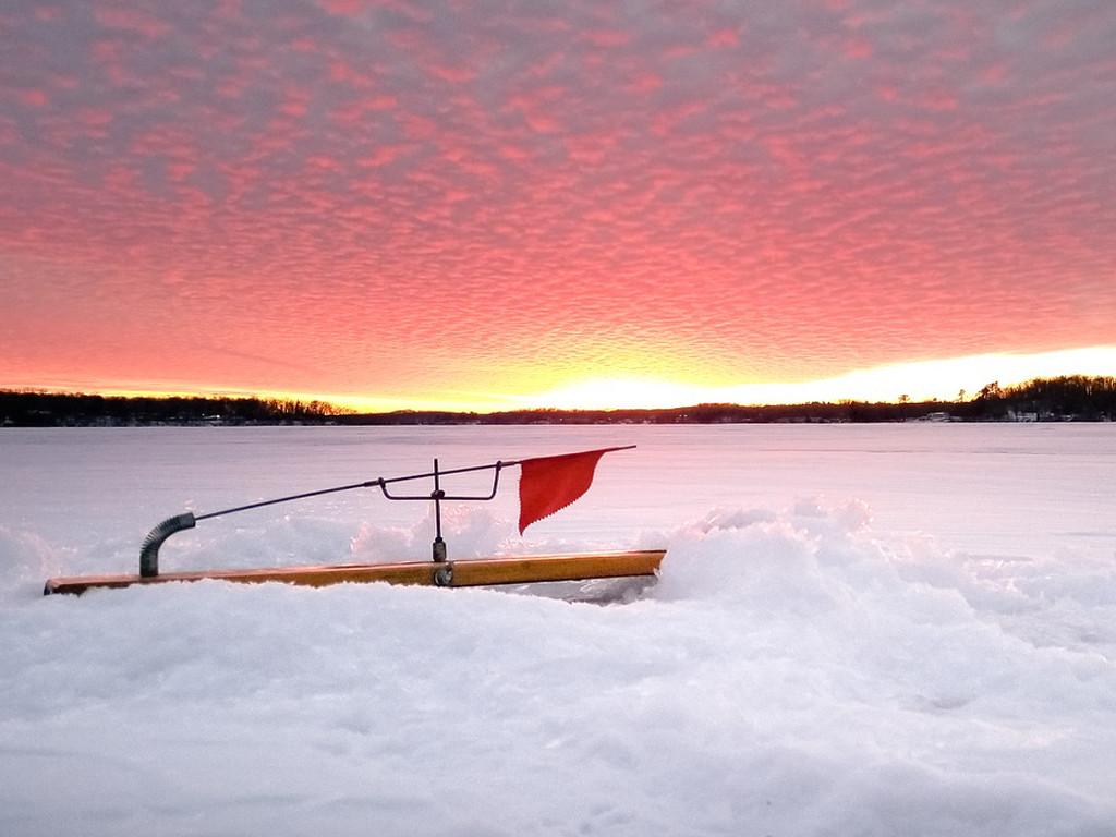 Angling på sjön mitt i vintern med solnedgång.